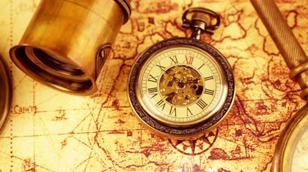 navigáció : Vintage magnifying glass, compass, telescope and a pocket watch lying on ancient world map in 1565. Stock mozgókép