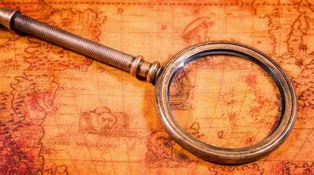 tesouro : Vintage still life. Vintage magnifying glass lies on an ancient world map in 1565