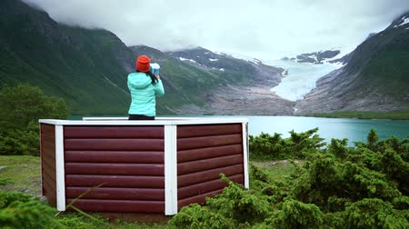 northen : Girl tourist looks at a glacier on the viewing platform. Svartisen Glacier in Norway. Stock Footage