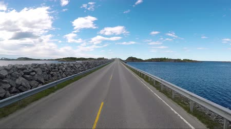 norueguês : Driving a Car on a Road in Norway The Atlantic Ocean Road or the Atlantic Road (Atlanterhavsveien) was awarded the title as (Norwegian Construction of the Century).