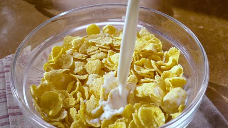 pouring : Crispy yellow corn flakes in the bowl for the morning a delicious breakfast with milk. Slow motion with rotation tracking shot. Stock Footage