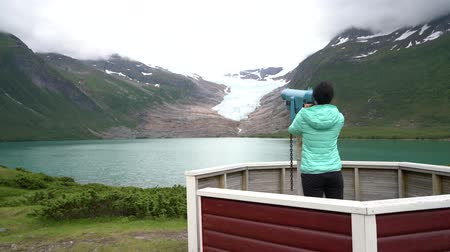 Girl tourist looks at a glacier on the viewing platform. Svartisen Glacier in Norway. Dostupné videozáznamy