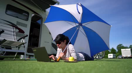wi fi : Woman looking at the laptop near the camping. Caravan car Vacation. Family vacation travel, holiday trip in motorhome RV. Wi-fi connection information communication technology.