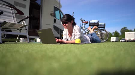 caravan : Woman looking at the laptop near the camping. Caravan car Vacation. Family vacation travel, holiday trip in motorhome RV. Wi-fi connection information communication technology.