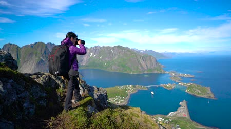 プロ : Nature photographer with camera shoots while standing on top of the mountain. Beautiful Nature Norway Lofoten archipelago. 動画素材