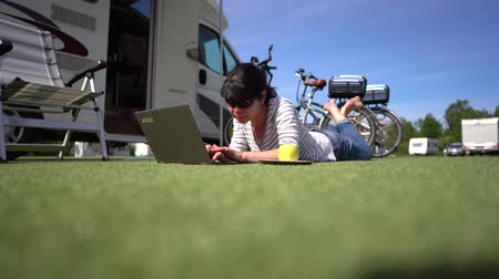 Woman looking at the laptop near the camping. Caravan car Vacation. Family vacation travel, holiday trip in motorhome RV. Wi-fi connection information communication technology.