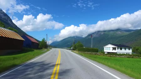 realtime : Driving a Car on a Road in Norway. In the background, the biker rides a motorcycle.