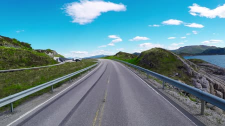 fiorde : Driving a Car on a Road in Norway The Atlantic Ocean Road or the Atlantic Road (Atlanterhavsveien) was awarded the title as (Norwegian Construction of the Century).