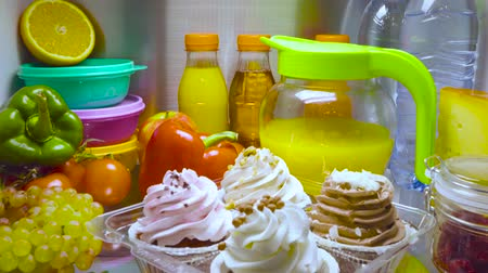 ataque : Sweet cakes in the open refrigerator. Products in the refrigerator.