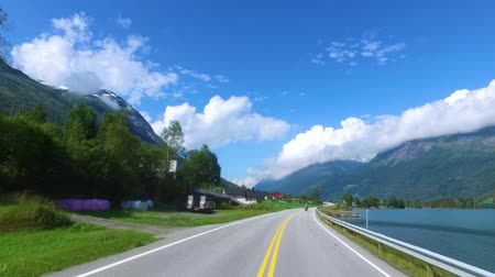 államközi : Driving a Car on a Road in Norway. In the background, the biker rides a motorcycle.