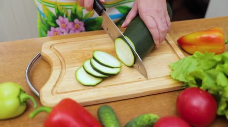 ингредиент : Womens hands Housewives cut with a knife fresh zucchini on the cutting board of the kitchen table