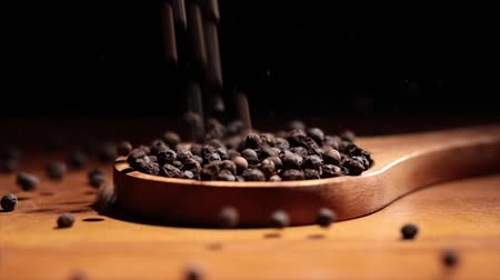 pimenta em grão : Black Tellicherry peppercorns closeup in wooden spoon on a kitchen table. Stock Footage