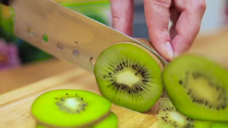 carving : Womens hands Housewives cut with a knife fresh kiwi on the cutting board of the kitchen table