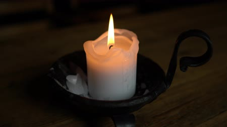 свечи : Candle in a candlestick on a wooden table Стоковые видеозаписи
