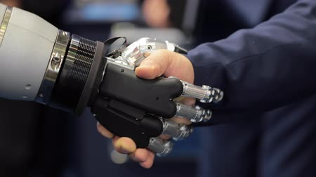 nobreza : Hand of a businessman shaking hands with a Android robot. The concept of human interaction with artificial intelligence.