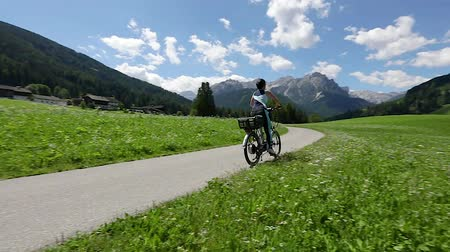 treadle : Woman on electric eco bike cycling Italy Dolomites Alps
