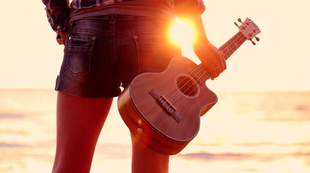 тусклый : Woman at sunset holding a ukulele