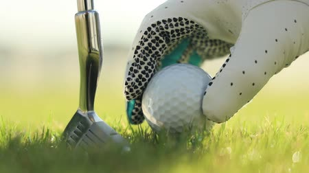 t şeklinde : Hand in glove placing golf ball on tee Stok Video