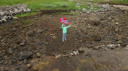 fiorde : Woman with a waving flag of Norway on the mini planet background of nature Stock Footage