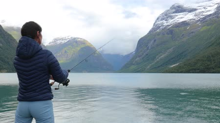 снасти : Woman fishing on Fishing rod spinning in Norway. Fishing in Norway is a way to embrace the local lifestyle. Countless lakes and rivers and an extensive coastline means outstanding opportunities...