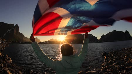 citizenship : Woman waving the flag of Norway at sunset background Stock Footage