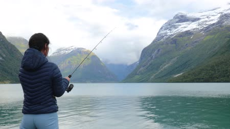 rozsáhlý : Woman fishing on Fishing rod spinning in Norway. Fishing in Norway is a way to embrace the local lifestyle. Countless lakes and rivers and an extensive coastline means outstanding opportunities...