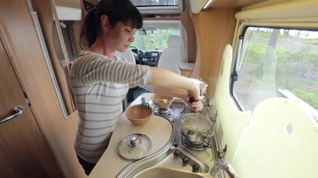 treyler : Woman cooking in camper, motorhome RV interior. Family vacation travel, holiday trip in motorhome, Caravan car Vacation.