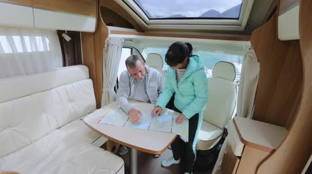 rving : Couples in RV Camper looking at the local map for the trip. Family vacation travel, holiday trip in motorhome, Caravan car Vacation. Stock Footage