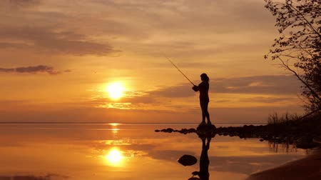 blue red : Woman fishing on Fishing rod spinning at sunset background.