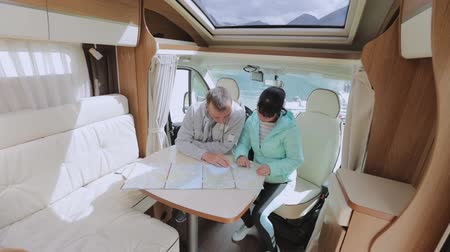 gezi : Couples in RV Camper looking at the local map for the trip. Family vacation travel, holiday trip in motorhome, Caravan car Vacation. Stok Video