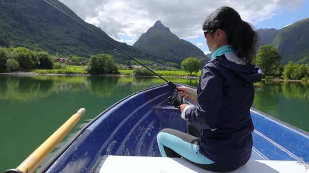 rozsáhlý : Woman on the boat catches a fish on spinning in Norway. Fishing in Norway is a way to embrace the local lifestyle. Countless lakes and rivers and an extensive coastline means outstanding opportunities Dostupné videozáznamy