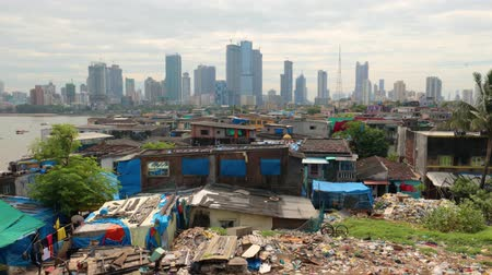 bombay : Views of slums on the shores of mumbai, India against the backdrop of skyscrapers under construction Stock Footage