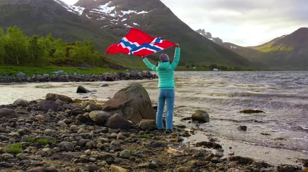 noors : Woman with a waving flag of Norway on the background of nature Stockvideo