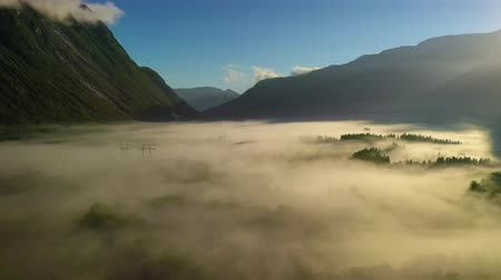 humedad : Morning mist over the valley among the mountains in the sunlight. Fog and Beautiful nature of Norway aerial footage.