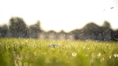 golfspieler : Golf club hits a golf ball in a super slow motion. Drops of morning dew and grass particles rise into the air after the impact.