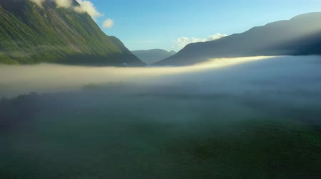 влажность : Morning mist over the valley among the mountains in the sunlight. Fog and Beautiful nature of Norway aerial footage.