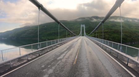 államközi : Driving a Car on a Road in Norway. Vehicle point-of-view driving over the bridge.