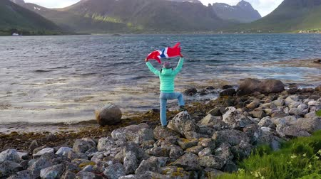 triunfar : Woman with a waving flag of Norway on the background of nature Vídeos