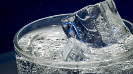 ice cube : Glass of water with ice on a dark blue background Stock Footage