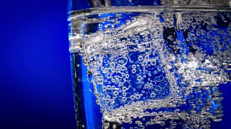 Glass of water with ice on a dark blue background Dostupné videozáznamy