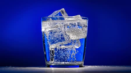 zasklený : Glass of water with ice on a dark blue background Dostupné videozáznamy