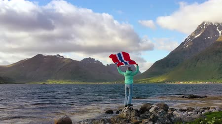 Woman with a waving flag of Norway on the background of nature Dostupné videozáznamy