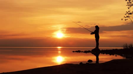 finland : Woman fishing on Fishing rod spinning at sunset background.