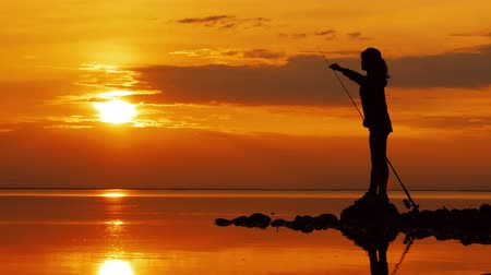 снасти : Woman fishing on Fishing rod spinning at sunset background.