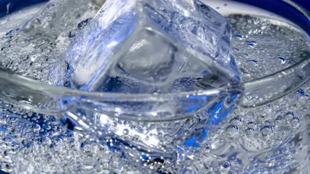 Glass of water with ice on a dark blue background Стоковые видеозаписи