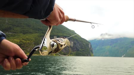 Woman fishing on Fishing rod spinning in Norway. Fishing in Norway is a way to embrace the local lifestyle. Countless lakes and rivers and an extensive coastline means outstanding opportunities