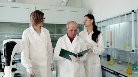 medical student : The academic group making clinical expertise. Old male person write discovery results, two laboratory assistants telling analysis and going near. The light procedural room with people and test-tubes