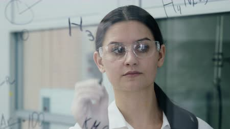 health test : Adult girl after clinical expertise write on the glass discovery way and structural solution of medicaments. Female teacher explaining to pharmacist students pharmaceutical development in university Stock Footage