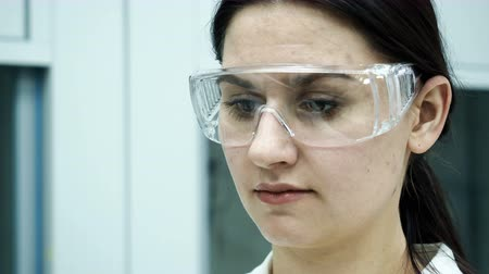 проверка : One caucasian beautiful laboratory assistant making clinical expertise, discovery molecular reaction in test-tube close up. Female person in protective safety mask holding pipet and dropping substance Стоковые видеозаписи