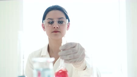 биохимия : One caucasian beautiful laboratory assistant making clinical expertise, discovery molecular reaction in test-tube close up. Female person in protective safety mask holding glasses and look at color